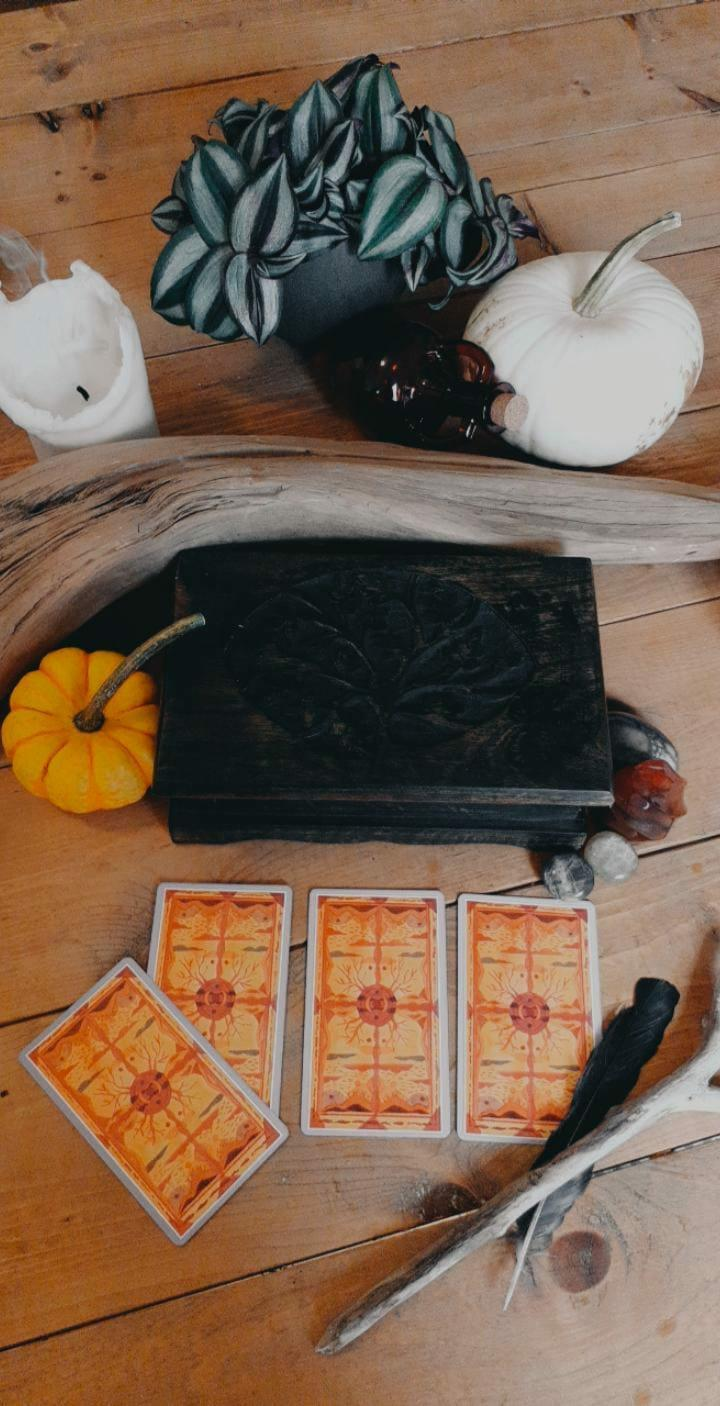 Tarot cards, candle, pumpkins, and other ritual items for Samhain